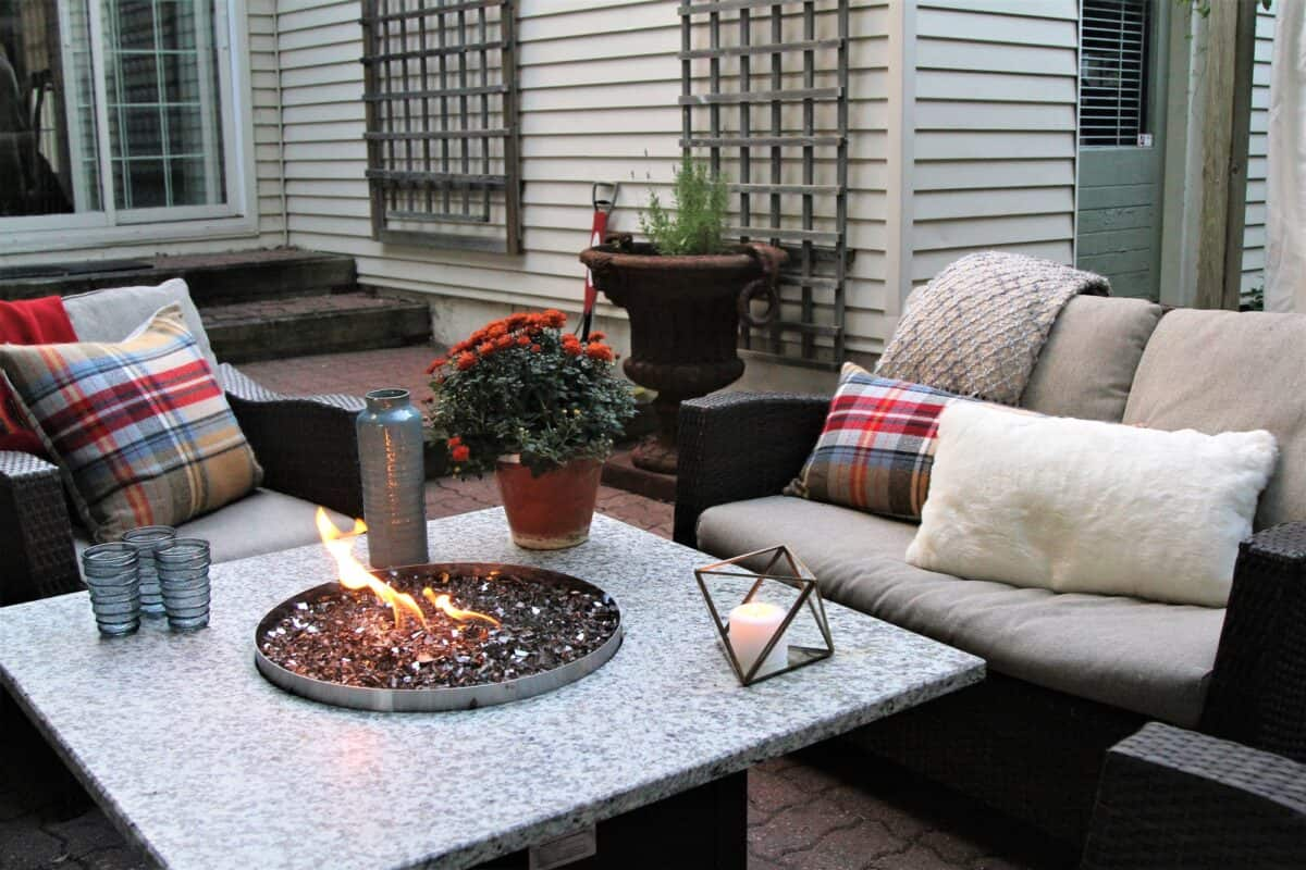 Backyard patio area with two patio chairs with cushions and a gas fire pit table between them.