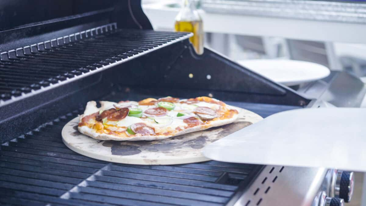 Pizza stone with homemade pizza on top of a bbq grill with a wooden pizza flipper coming into frame.