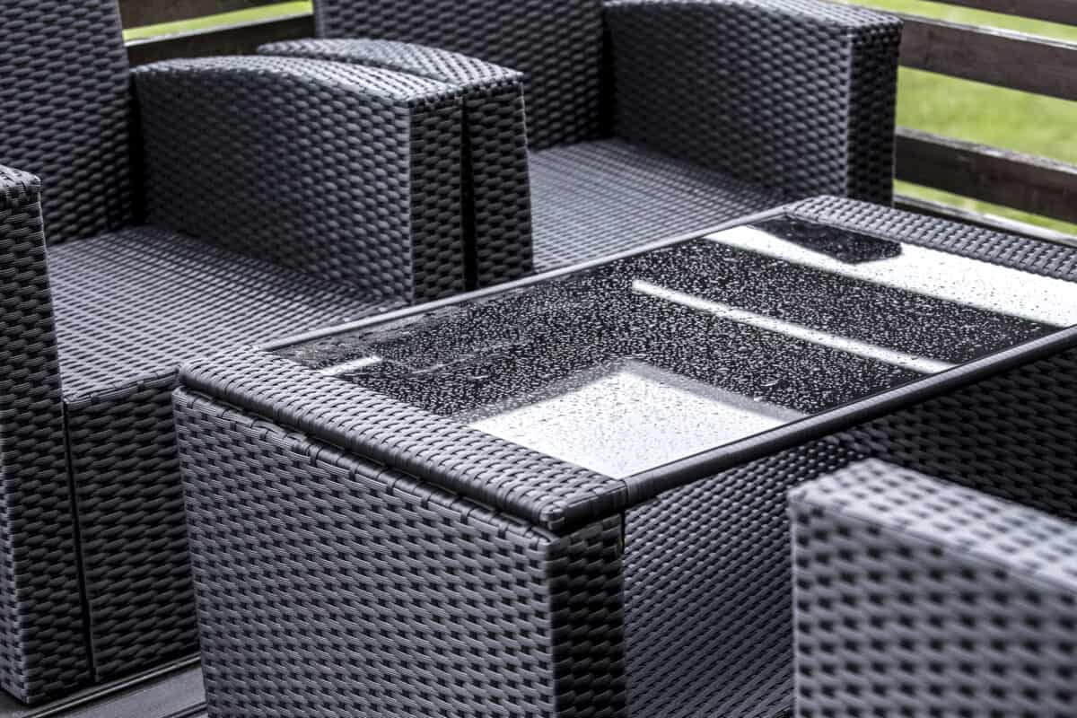 Outdoor wicker patio furniture with glass table wet from the rain