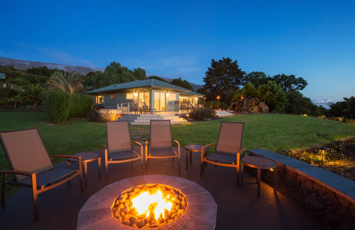 Outdoor fire pit with chairs surrounding it and a house in the background