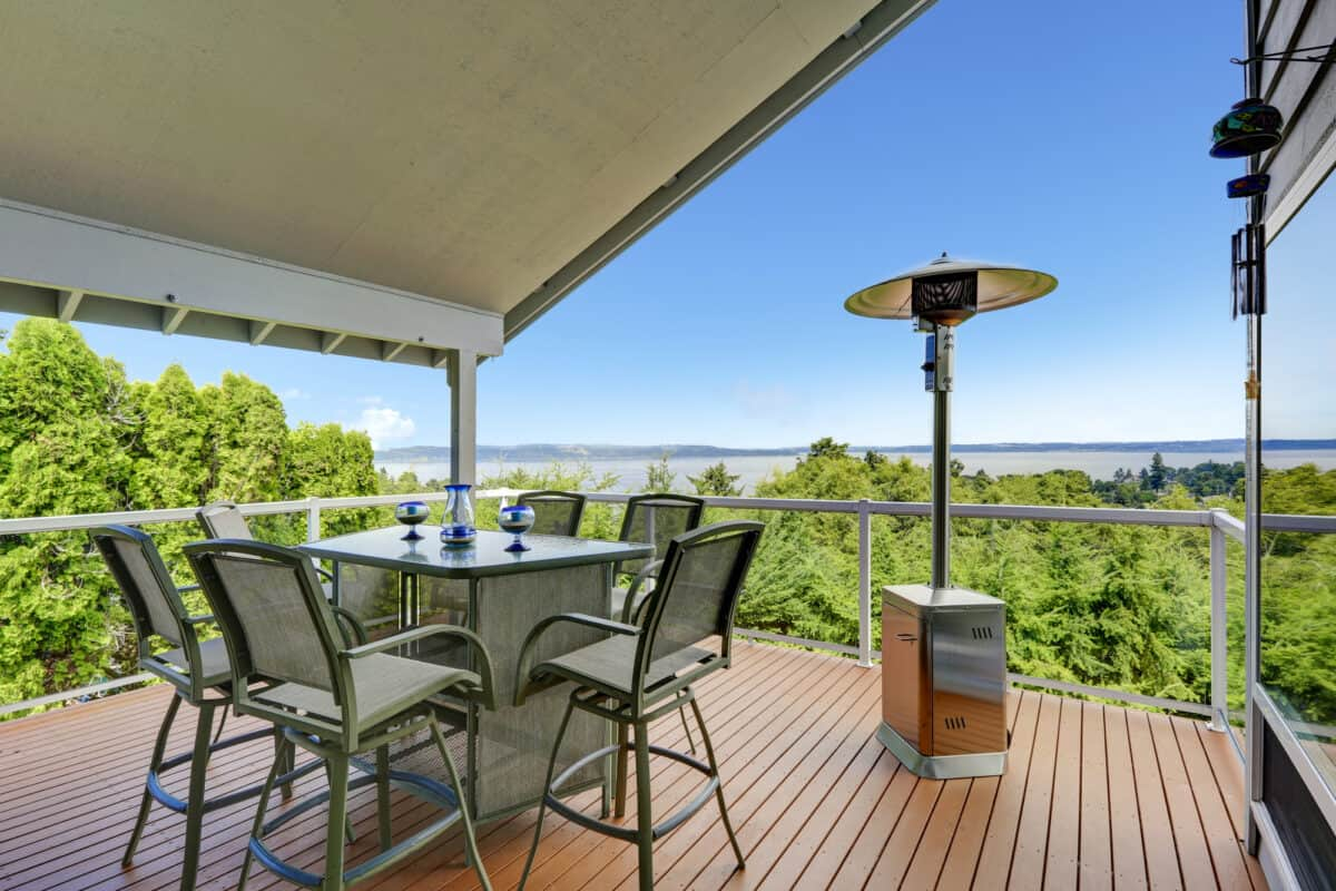Patio heater to the side of chairs and table overlooking trees and lake.