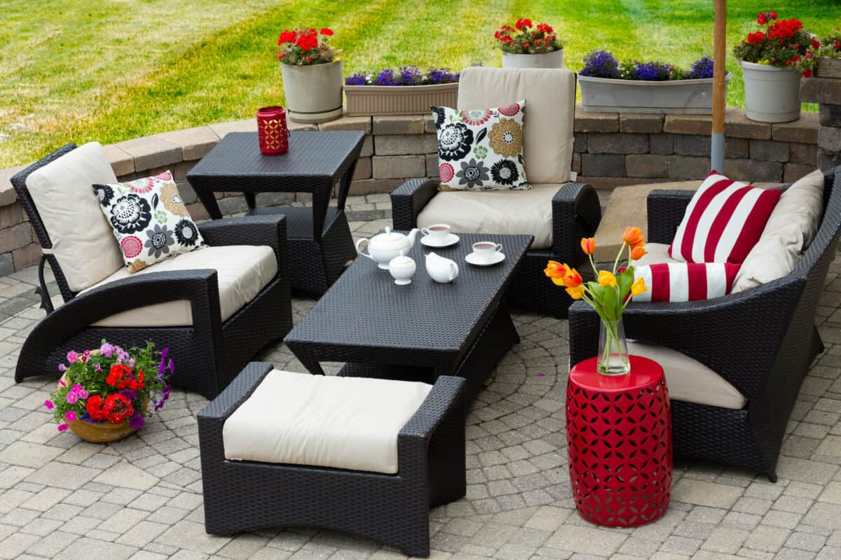 Patio furniture with patio cushions around a wicker table that has tea cups and a tea pot. Arranged flowers surround the patio.