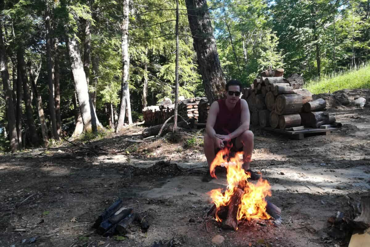 Stuart, the founder of livingtheoutdoorlife.com, sitting in front of a fire demonstrating an unsafe firepit at his cottage, flaming wood on top of flat ground.