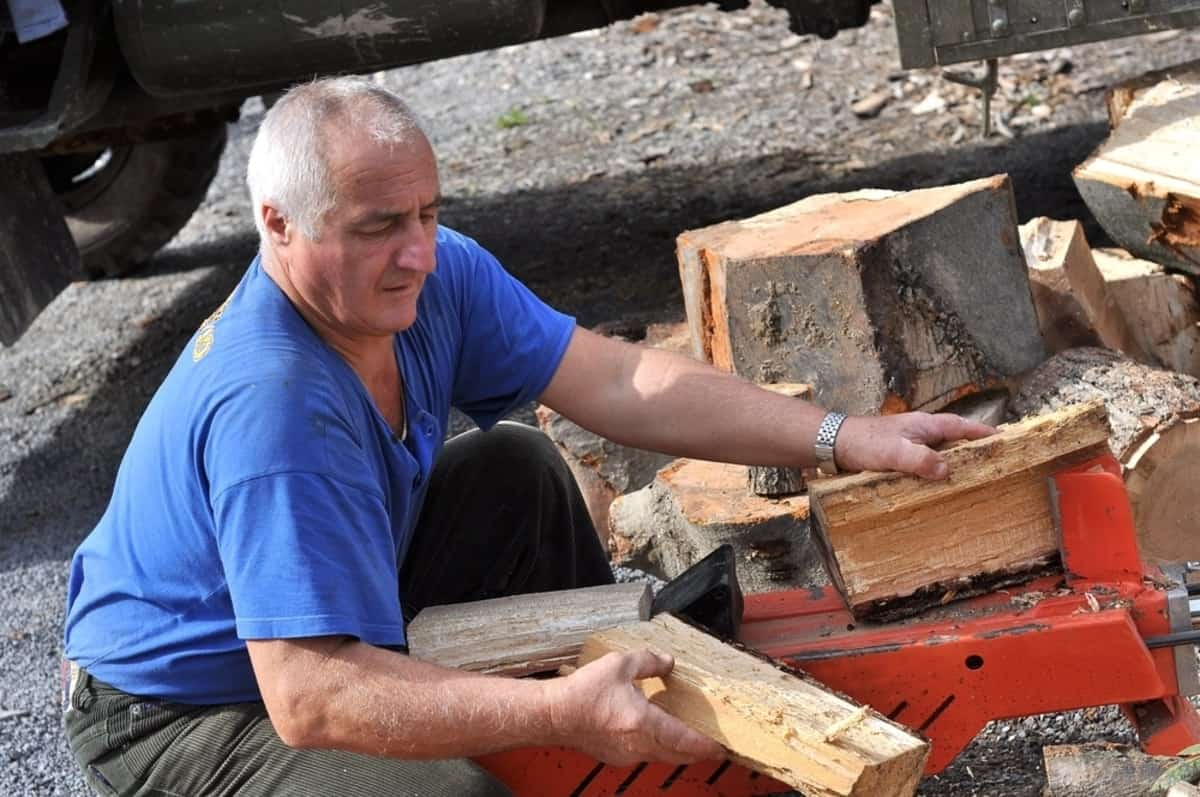 man operating dangerous machine, log splitter, to cut wood
