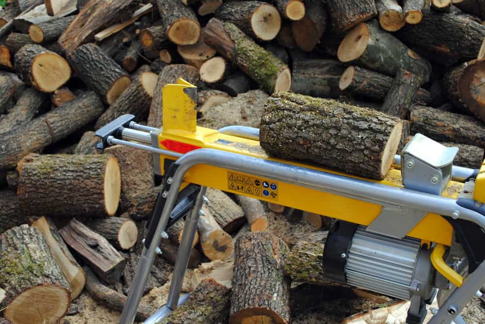 Close up of log splitter with a pile of logs in the background ready to be split.