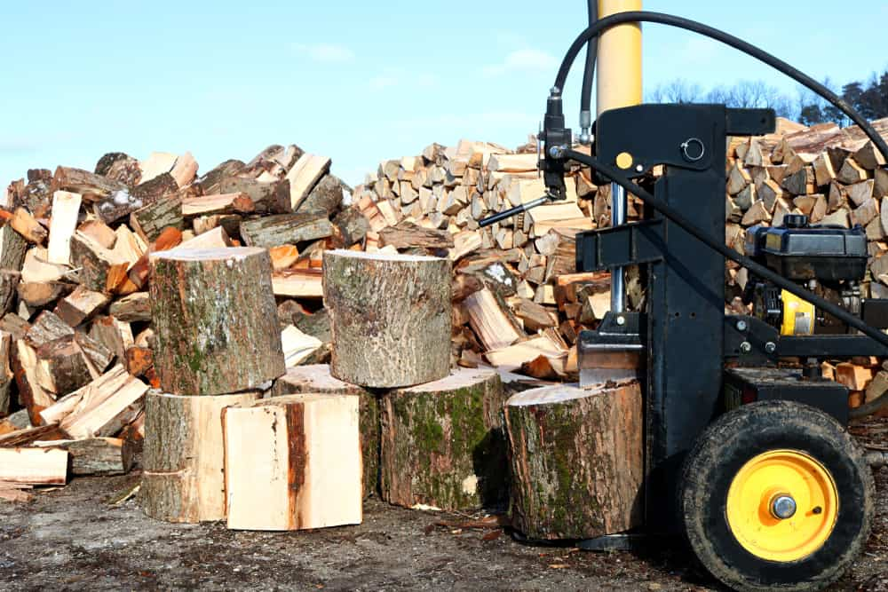 Hydraulic log splitter splitting large pieces of wood with big piles of split wood in background