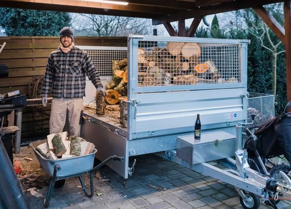 A large size pile of firewood on trailer hitch with man unloading wood while smiling at camera.