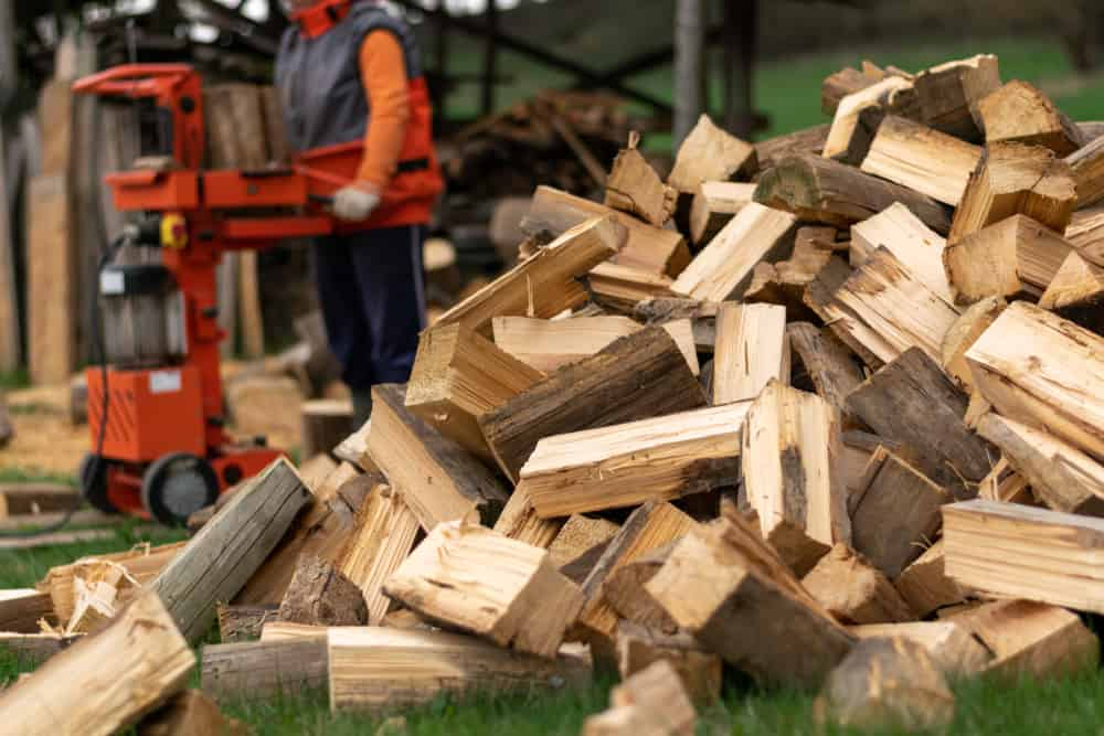 Pile of split wood with a man operating a wood splitter in the background