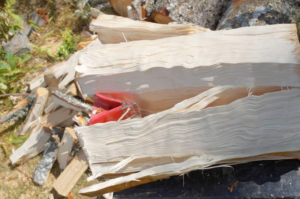 Wood being split using a log splitter wedge, close up picture with stack of split wood in background.
