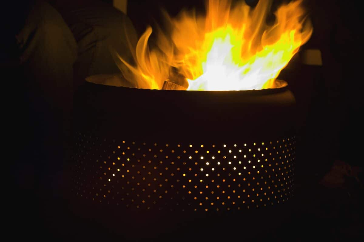 fire pit with holes burning wood