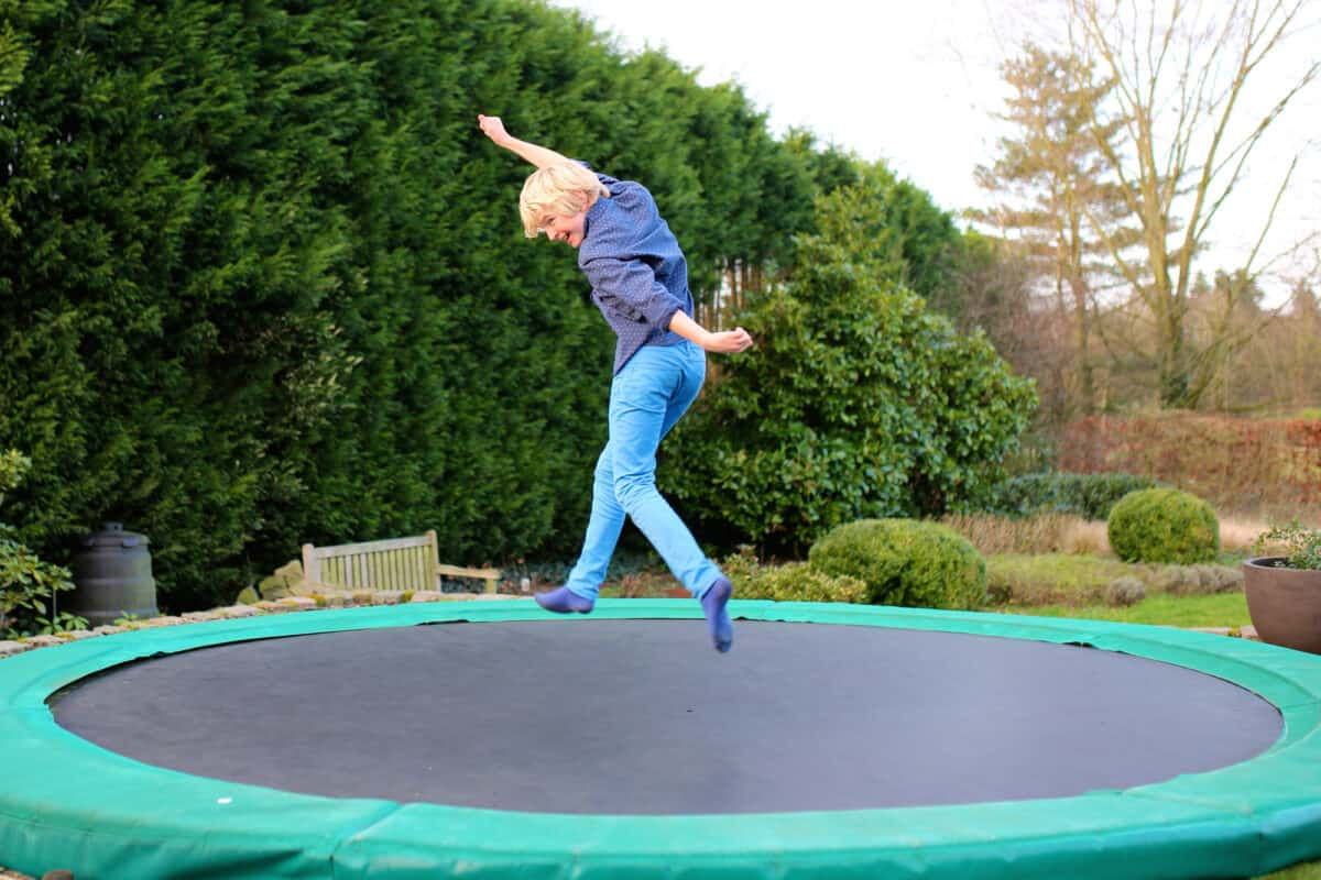 Happy kid plays outdoors in garden jumping high in the sky on trampoline. Active teenager boy having fun outdoors at early spring day.