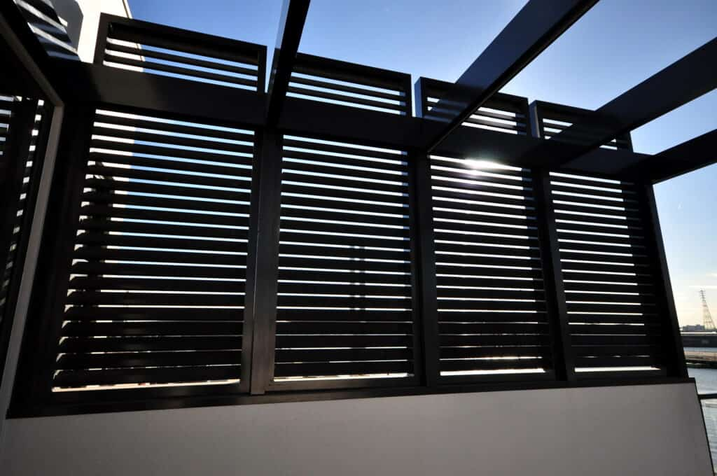 Metal pergola blocking out sun on side of home
