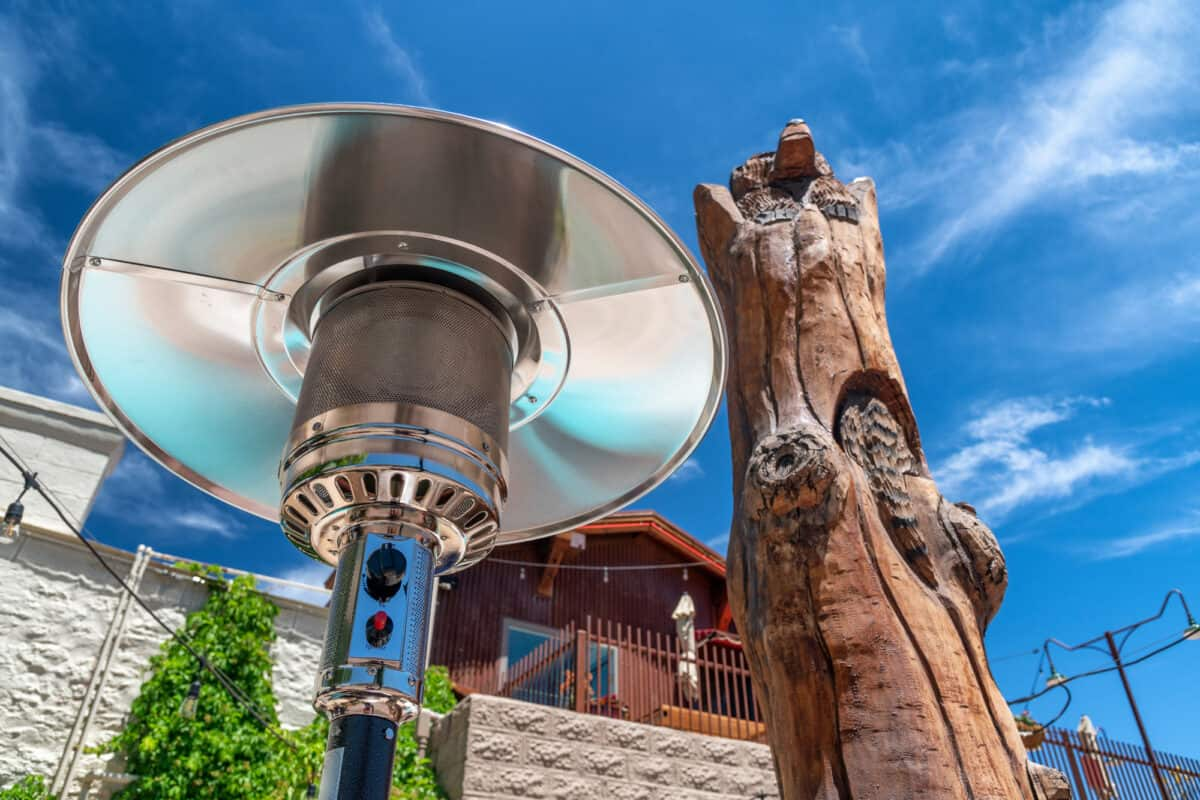 Electric stainless steel metal gas burning outdoor patio heater along with tree trunk on the Route 66.