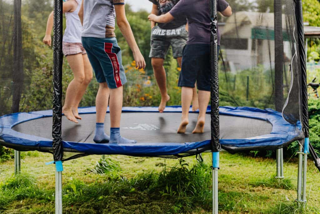 children jumping on trampoline with net in backyard outdoors