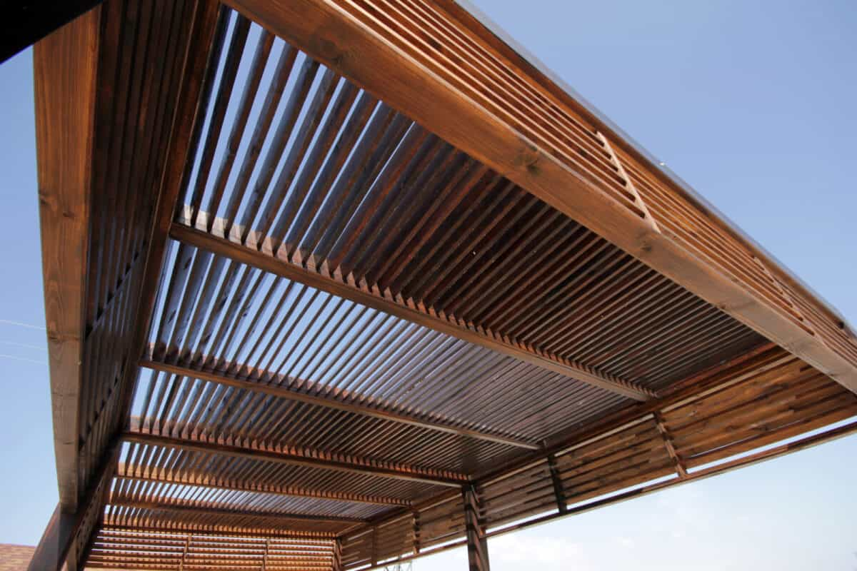 Close up of wooden louvered pergola with sky in background
