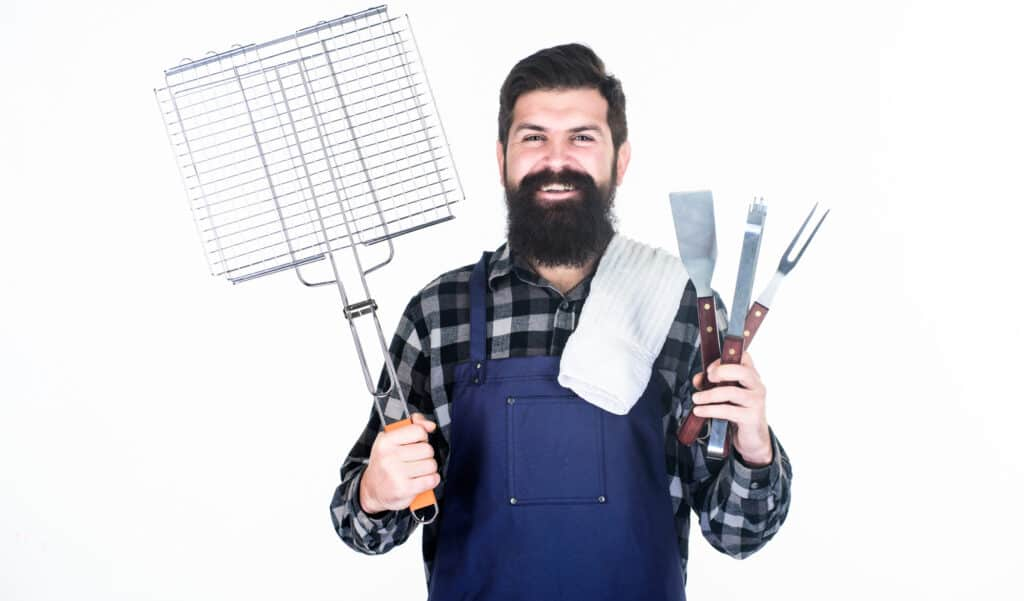Your satisfaction guaranteed with cooking tool set. Happy hipster holding stainless steel tools. Bearded man with barbecue tools in hands. Grill cook using tool set with spatula and grilling fork.