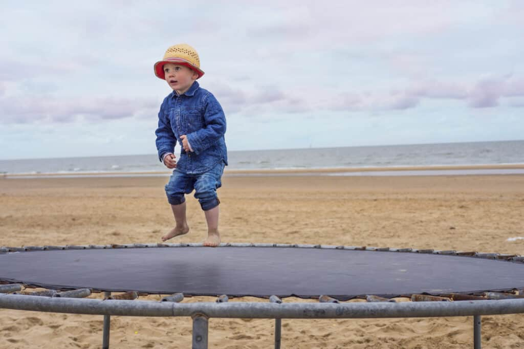 A child apprximately 2-year old jumping on a trampoline on a beach with water in background