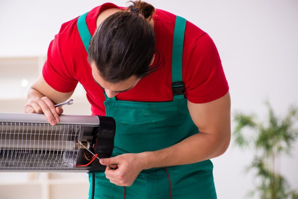 Man in uniform bent over fixing patio heater problems with tools