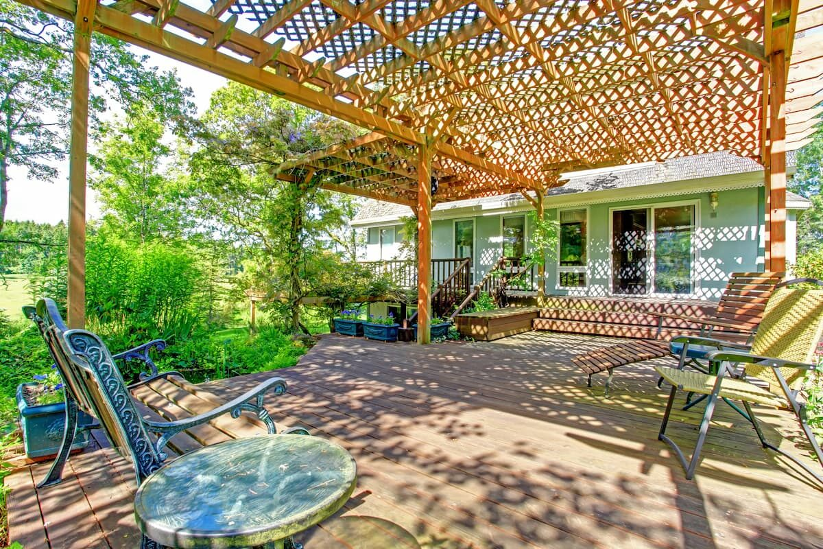 Picture of large backyard patio with excellent shade coverage from a pergola  showcasing the many reasons to own a pergola for backyard beauty and shade coverage
