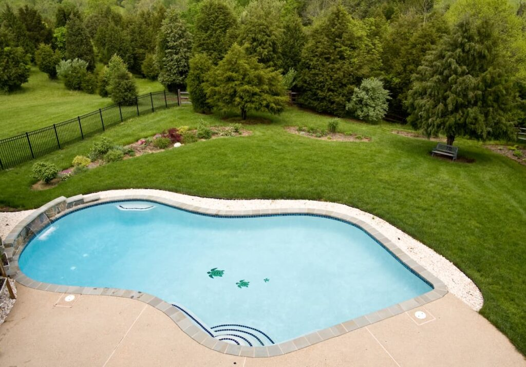Large pool in backyard with pool water next to the grass