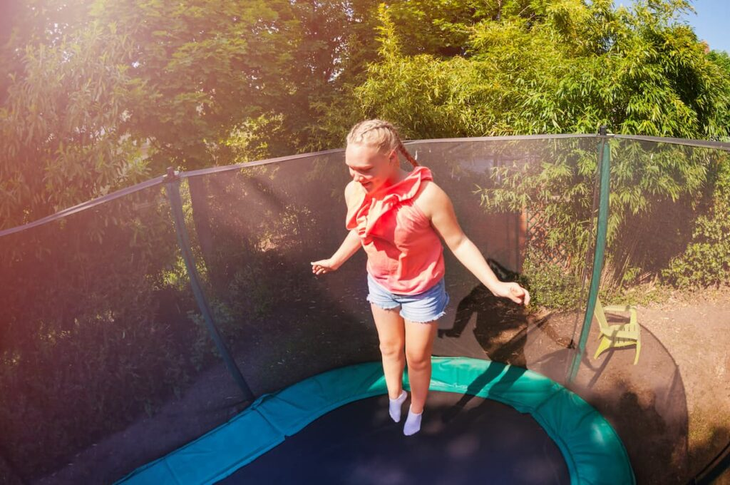 Girl jumping on a trampoline in backyard on concrete