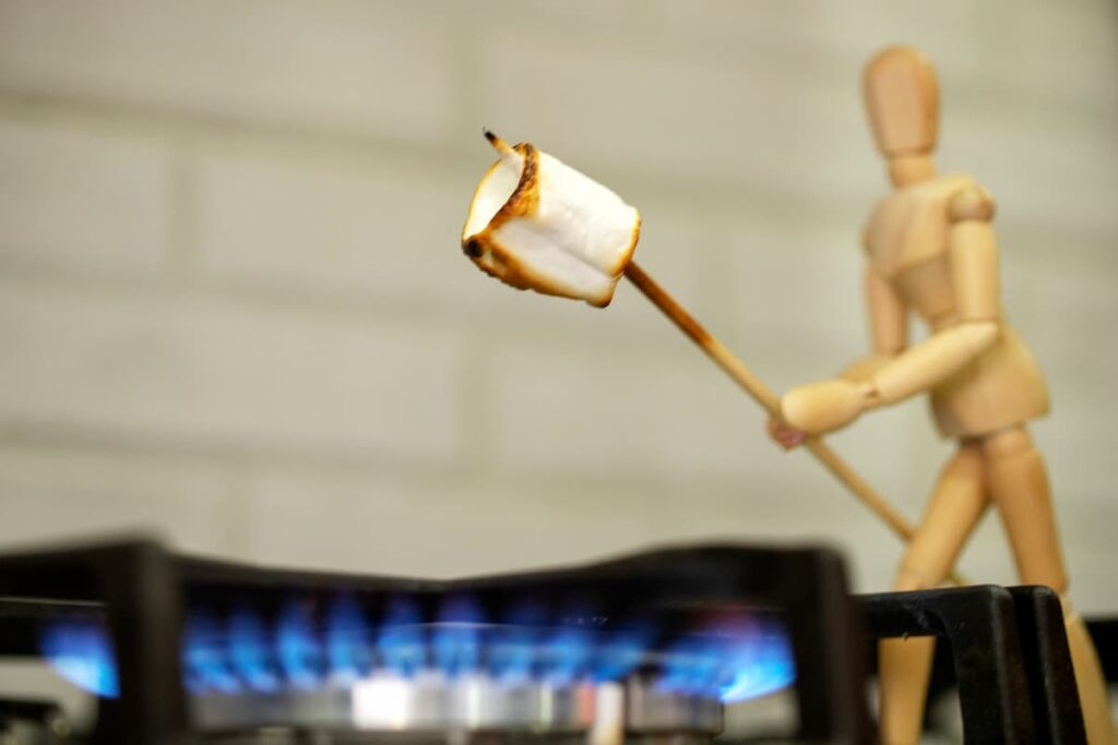 stick figure roasting marshmallow over gas fire on stove